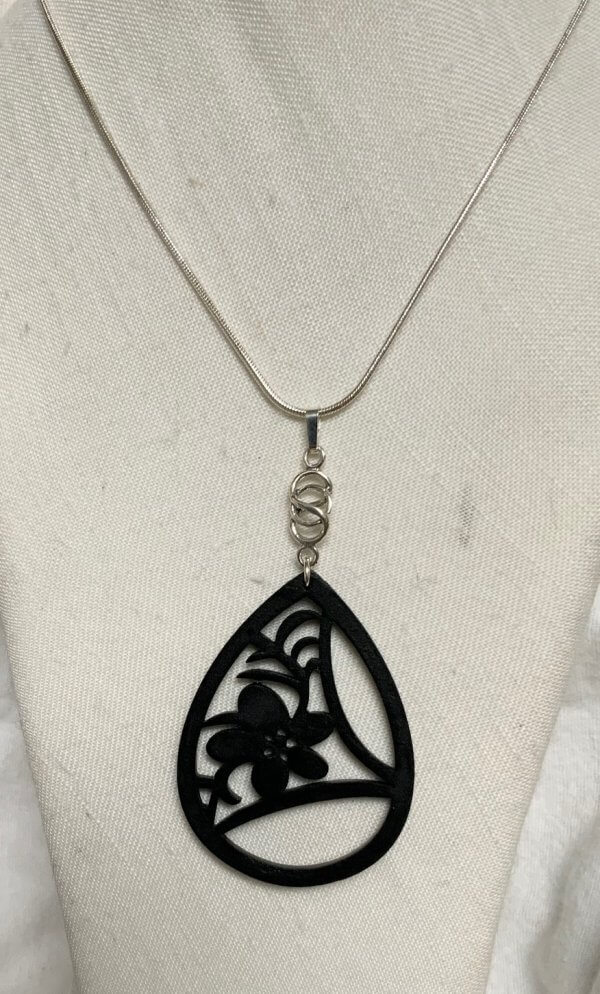 Indian carved wood, and sterling silver pendant